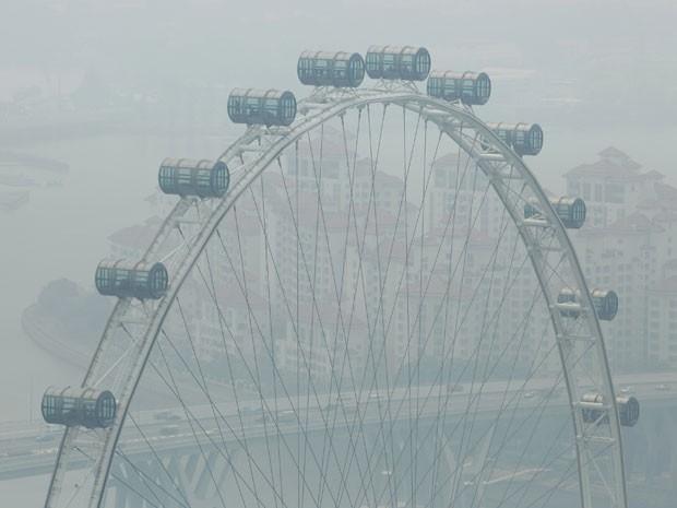 Reprodução: globo.com (Edgar Su/ Reuters) - Singapore Flyer é encoberto pela poluição